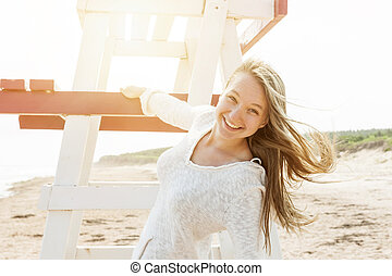 Carefree young woman on beach - Young carefree woman with...