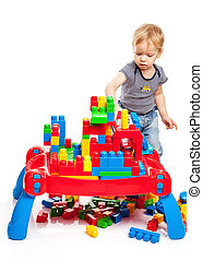 Toddler boy playing with building blocks on white background