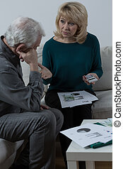 Discussing couple - Senior couple discussing about financial...