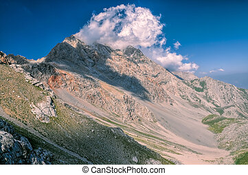Kyrgyzstan - Scenic mountain peaks with forming clouds in...