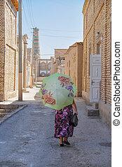 Woman in Uzbekistan - Uzbek woman with parasol walking down...