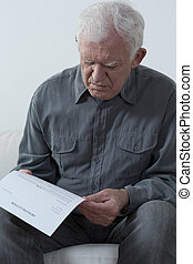 Credit summary - Worried aged man reading his credit summary
