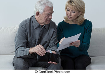 Checking the balance - Older troubled married couple...