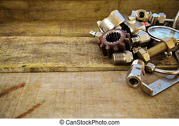 Old machine parts in machinery shop on wooden background