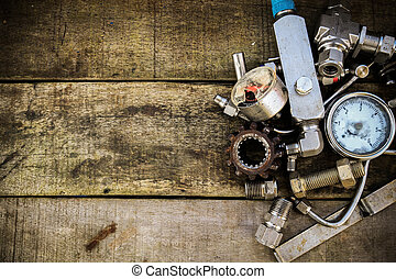 Old machine parts in machinery shop on wooden background.old...