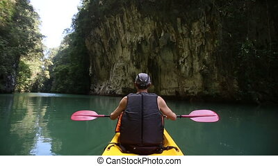 man floats kayak and looks around kayak - elderly man smile...