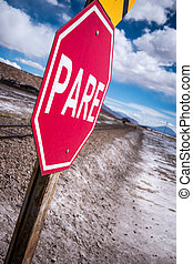 Stop sign (pare) at railway crossing in a desolate landscape...