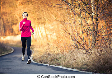 Young woman running outdoors in a city park on a cold...