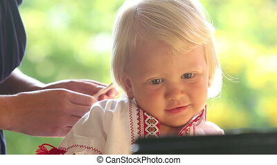 mother combing blonde small smiling girl closeup