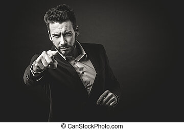 Aggressive businessman pointing finger against dark...