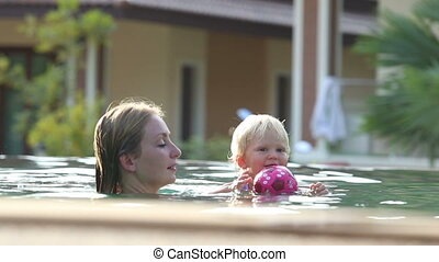small blonde child swim with mother