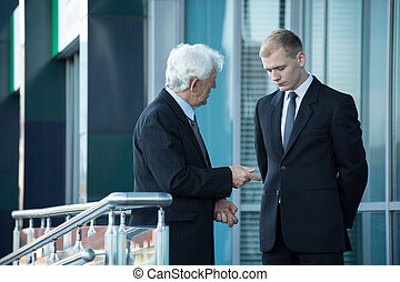 Senior businessman talking with his employee - Close-up of...