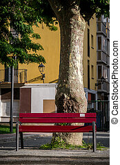 Red park bench in urban setting - A red park bench sits...