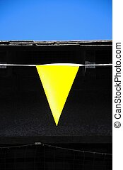 Yellow pennant - Yellow pennant flag against a roof edge