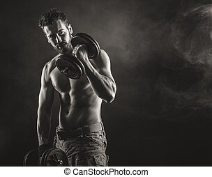 Male body builder working out with dumbbells - Male...
