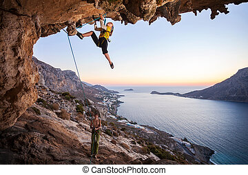Seven-year old girl climbing a challenging route, father...