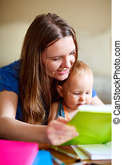 Family at home - Young mother and her baby daughter reading...