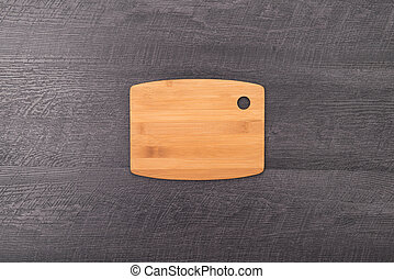 Cutting board on wooden background.
