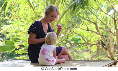 mother blowing bubbles for daughter