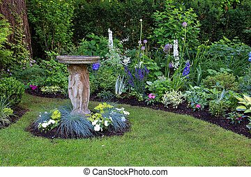 Bird bath by flower bed. - Bird bath in a beautiful summer...