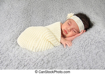 Newborn baby girl wearing a lace head band.