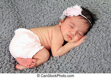 Newborn baby girl wearing a knitted hat.