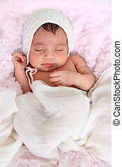 Newborn baby girl wearing a knitted hat