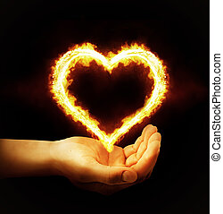 Hand holding fire heart on black background. Saint...