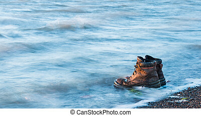 Water Work Boots - Pair of work boots in water on a beach