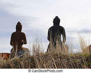 Two Stone Buddhas in Silhouette from the Back