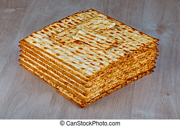 Matzah - Closeup of Matzah on wooden table which is the...
