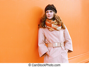 Pretty woman in coat posing against colorful wall
