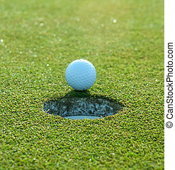 Ball at Edge of Hole Close Up - A golf ball rests on the...