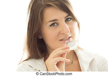brunette woman holding packed condom against white...