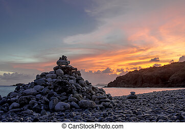 Cairn on Rock Beach Light - Sunset falls over a rocky beach...