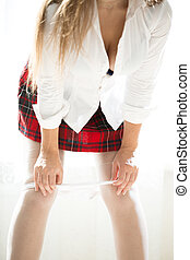 woman in red checkered skirt and white shirt taking off lace...