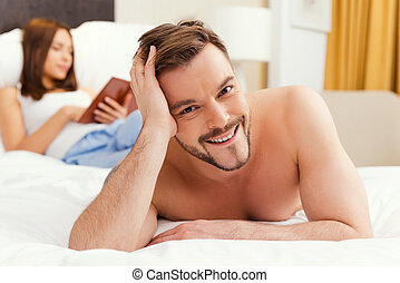 Feeling just happy Handsome young and shirtless man lying in...