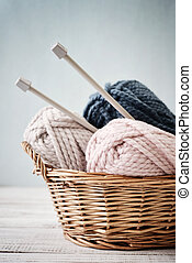 Wool yarn in coils with knitting needles in wicker basket on...