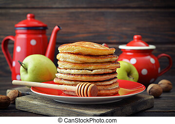 Stack of pancakes on plate with vintage teapots and fresh...