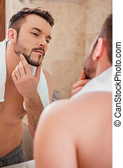 To shave or not to shave. Handsome young man touching his...