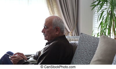 Senior Man Watching Television and using Remeto Control at...