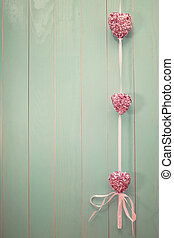 Pink shiny hearts on vintage green wood background - Pink...