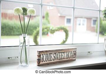 home sweet home - on a window sill in the house is a sign...