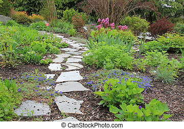 Spring garden path - Beautiful paved stone walkway in a...