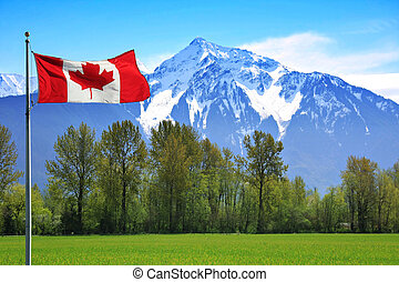 Rocky mountains - Canadian flag in front of te snow capped...