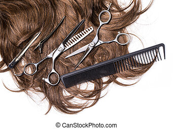 Long brown hair with scissors on close up isolated on white...