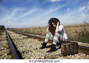 Woman with suitcase on railway