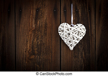 White wicker heart on wooden background