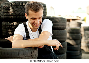 Young mechanic laughing outside car service