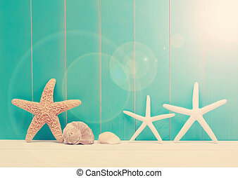Starfish and sea shells on a teal wooden background -...